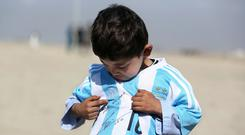 Afghan Lionel Messi fan Murtaza Ahmadi poses for a photograph, as he wears a shirt signed by Messi, in Kabul, Afghanistan (Rahmat Gul/AP)