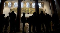 Visitors stand below a renovated part of a fresco inside the Church of the Nativity (Majdi Mohammed/AP)