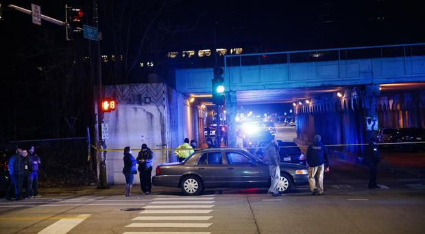 Police investigate the scene where two officers were killed after they were struck by a South Shore train (Armando L Sanchez/AP)