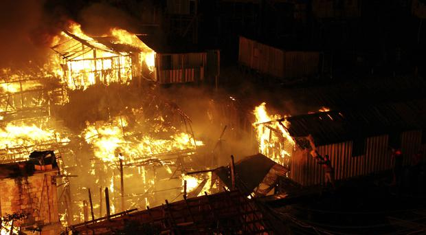 Homes are engulfed by a fire in the Educandos neighbourhood in Manaus, Brazil (Edmar Barros/AP)