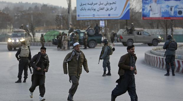 People run away from the site of a clash between insurgents and security forces in Kabul (Rahmat Gul/AP)