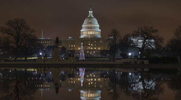 The US Capitol is mirrored in the Reflecting Pool in Washington as a partial government shutdown heads into a second week (J Scott Applewhite/AP)