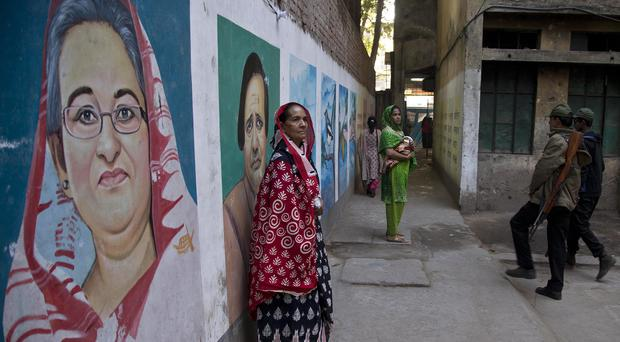 Bangladeshi women stand next to a mural displaying portraits of Bangladesh Prime Minister Sheikh Hasina, left, and others after casting their votes at a polling station in Dhaka (Anupam Nath/AP)