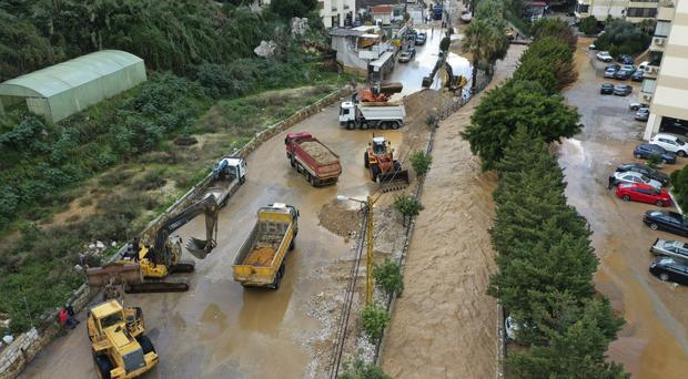 Bulldozers and trucks clear a street after rivers overflowed (Hussein Malla/AP)