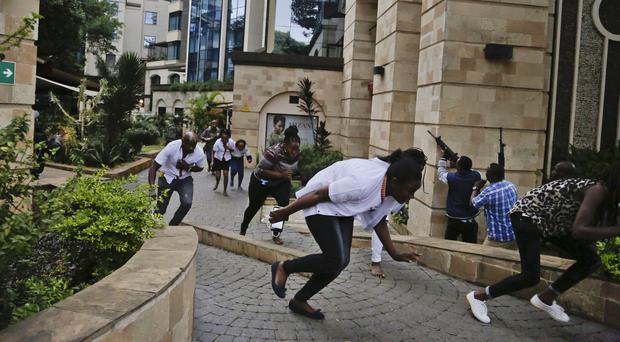 Civilians flee as security forces aim their weapons at the buildings of a hotel complex in Nairobi( Khalil Senosi/AP)