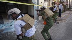 Security forces point their weapons through a shattered door at the hotel complex in Nairobi, (Ben Curtis/AP)