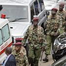 Kenyan security forces walk away from the hotel complex (Ben Curtis/AP)