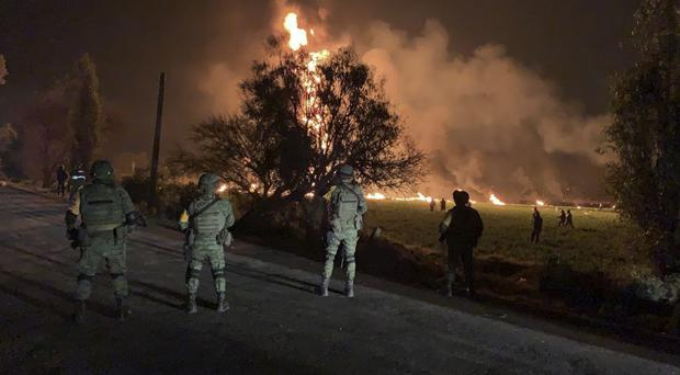 Soldiers guard the area around an oil pipeline explosion in Tlahuelilpan, Hidalgo state, Mexico (Secretary of National Defence via AP)