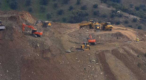 Drill machines and excavating machinery work next to a deep borehole (Gregorio Marrero/AP)