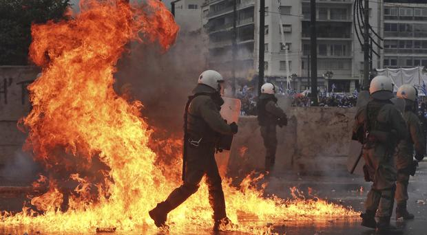 A molotov cocktail explodes next to Greek riot police during clashes after a rally in Athens (Yorgos Karahalis/AP)