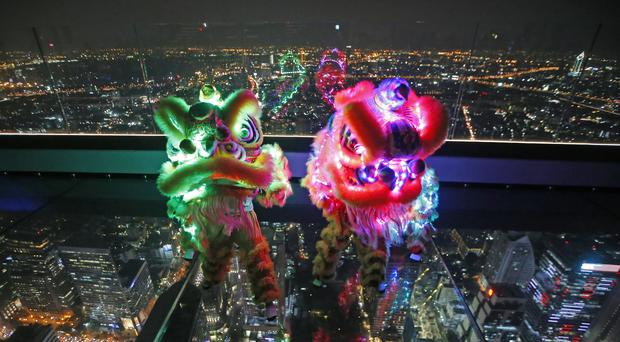 A lion dance with LED lights is performed on the glass deck of the King Power Mahanakhon building, currently Thailand's tallest, in Bangkok (AP Photo/Sakchai Lalit)