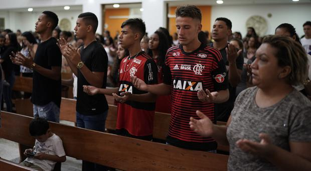 Flamengo youth players pray during a memorial Mass for the victims of a fire at the Brazilian football academy (Leo Correa/AP)