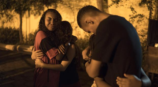 Friends embrace outside a church after attending a memorial Mass for the victims of a fire at a Brazilian soccer academy (AP)