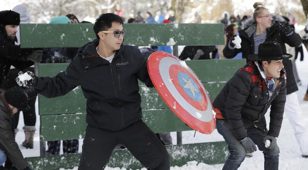 People armed themselves with shields while taking part in a public snowball fight in Tacoma, Washington (AP Photo/Ted S. Warren)