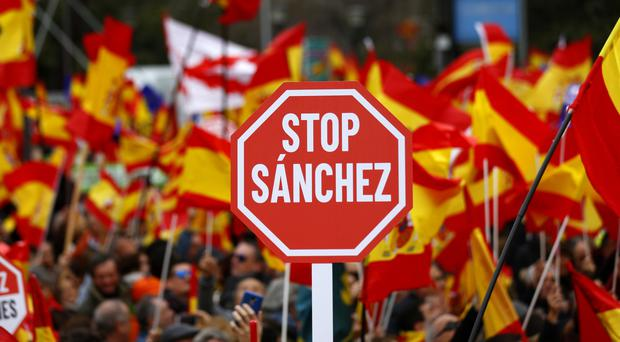 Demonstrators hold banners and Spanish flags (AP Photo/Andrea Comas)