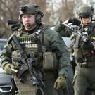 Police officers armed with rifles gather at the scene in Aurora (Antonio Perez/Chicago Tribune/AP)