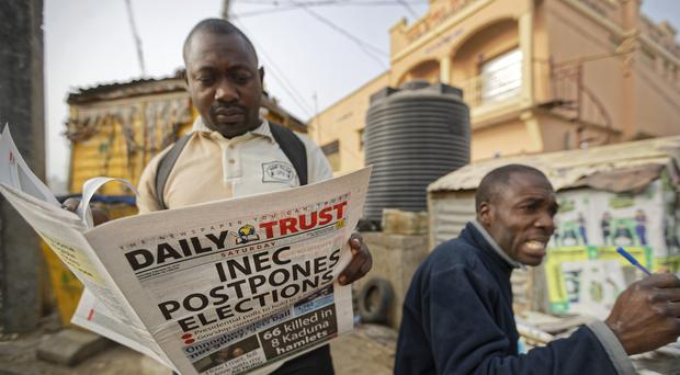 A man reads a copy of a newspaper which managed to print the news of the postponement of the presidential election (Ben Curtis/AP)