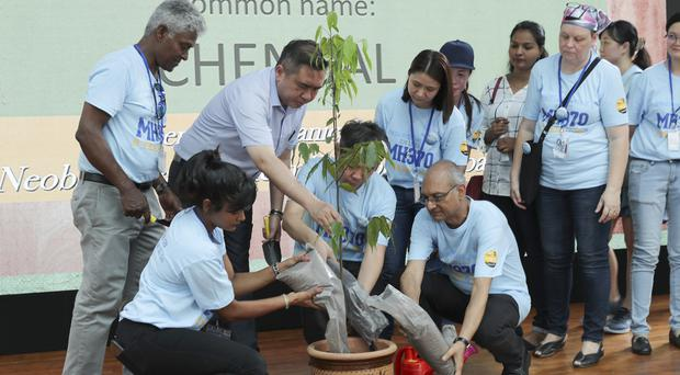 Malaysian Minister of Transport Anthony Loke plants a tree with family members of passengers of the missing Malaysia Airlines Flight MH370 (Vincent Thian/AP)