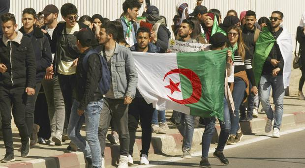Demonstrators march with Algerian national flags during a protest to denounce President Abdelaziz Bouteflika's bid for a fifth term (Fateh Guidoum/AP)