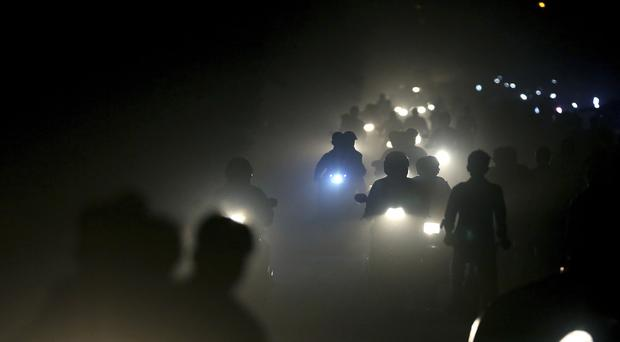 Motorists ride through a thick blanket of smog and dust on the outskirts of New Delhi, India (Altaf Qadri/AP)