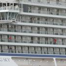Some of the remaining passengers look out as the cruise ship Viking Sky arrives at port off Molde (Svein Ove Ekornesvag/AP)