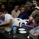 Supporters of the Pheu Thai party watch the election results broadcast (Gemunu Amarasinghe/AP)