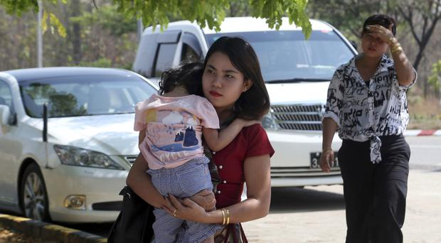 Chit Su Win, wife of Reuters journalist Kyaw Soe Oo, carries her daughter on arrival at the Supreme Court in Naypyitaw, Burma (Aung Shine Oo/PA)