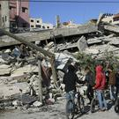 Residents inspect the damage of the destroyed multi-storey building of a Hamas-affiliated insurance company, in Gaza City (Adel Hana/AP)
