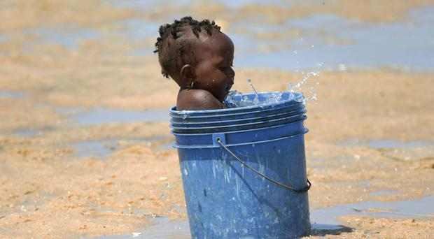 A baby plays with water in a bucket at a camp for displaced survivors of Cyclone Idai (Tsvangirai Mukwazhi/AP)