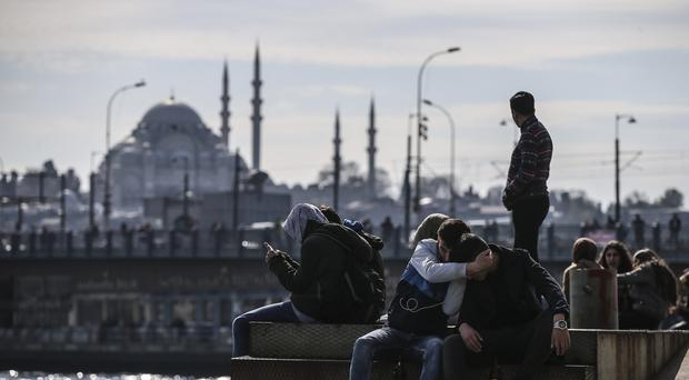 Backdropped by the Suleymaniye mosque, people sit by the Golden Horn in Istanbul (Emrah Gurel/AP)