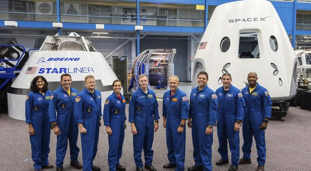 Mock-ups of Boeing's CST-100 Starliner and SpaceX's Crew Dragon capsules with crew members (Nasa/AP)