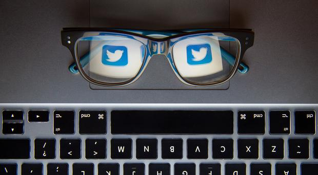 The logo of social network site Twitter reflected in a pair of glasses (Dominic Lipinski/PA)
