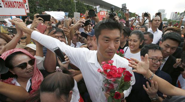 Thailand's Future Forward Party leader Thanathorn Juangroongruangkit is mobbed by supporters as he arrives at a police station in Bangkok to hear criminal charges of sedition against him filed by the ruling military junta (Sakchai Lalit/AP)