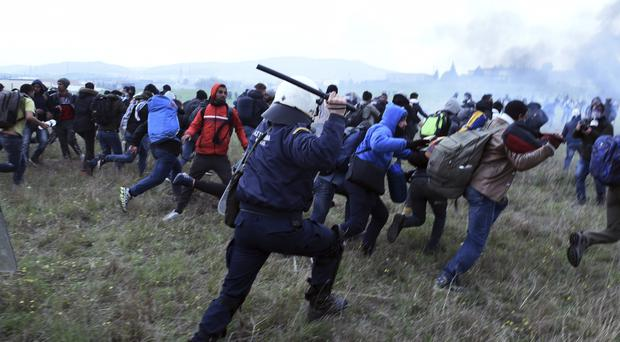 Riot police clash with protesting migrants outside a refugee camp in the village of Diavata, west of Thessaloniki, northern Greece (Giannis Papanikos/AP)