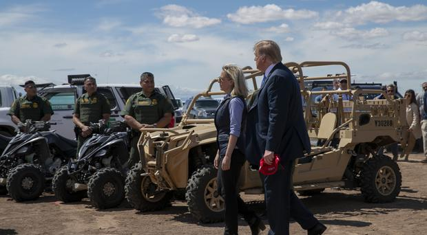 President Donald Trump walks with Homeland Security Secretary Kirstjen Nielsen as they visit a newly constructed part of a border wall with Mexico in Calexico, California (Jacquelyn Martin/AP)