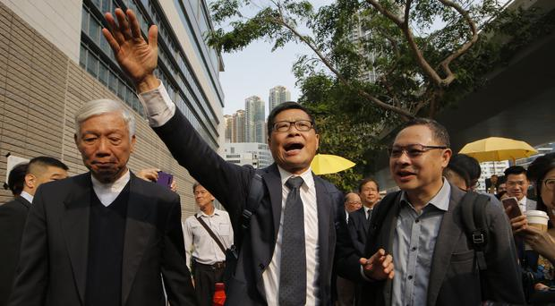 Occupy Central leaders, from right, Benny Tai, Chan Kin-man and Chu Yiu-ming wave to supporters before entering a court in Hong Kong (Kin Cheung/AP)