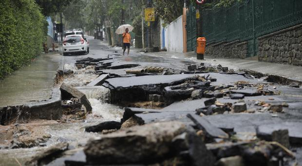 A man walks on a street damaged by heavy rains in the Jardim Botanico neighbourhood in Rio de Janeiro, Brazil (Silvia Izquierdo/AP)