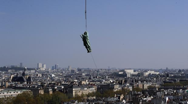 The religious statue representing St Andrew perched atop Paris's Notre Dame Cathedral descends to earth for the first time in over a century as part of a restoration (Francois Mori/AP)