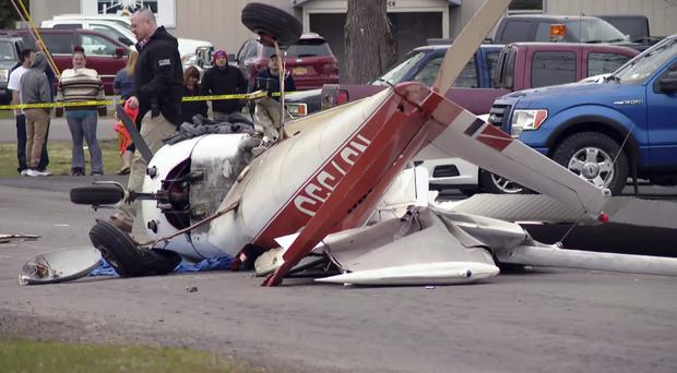 The wreckage of a light plane after it crash-landed on a street (CNYCENTRAL, SYRACUSE, NY, via AP)