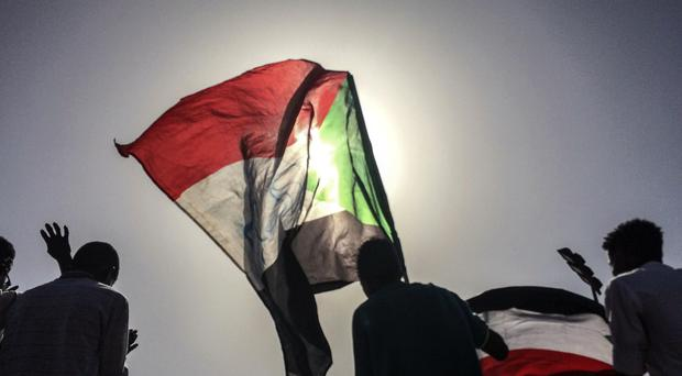 Sudanese demonstrators march with national flags (AP Photo)