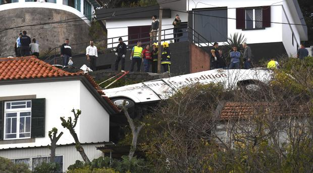 Rescue officials attend the scene after a tour bus crashed in Canico on Portugal's Madeira Island (Rui Silva/Aspress/Global Imagens/AP)