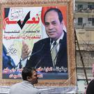 People walk past a banner supporting proposed amendments to the Egyptian constitution (Amr Nabil/AP)