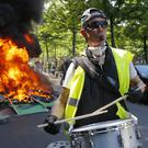 A man bangs a drum in front of a fire on the street during a yellow vest demonstration in Paris (Michel Euler/AP)
