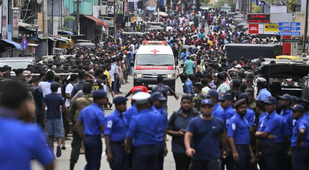 Police officers clear the road after explosions in Colombo (Eranga Jayawardena/AP)