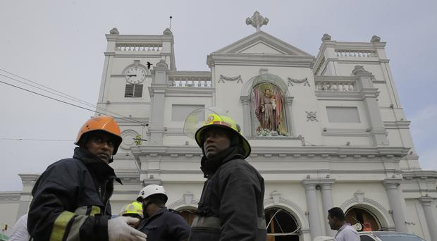 Sri Lankan firefighters stand in the area around St Anthony's Shrine (Eranga Jayawardena/AP)