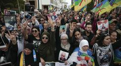 Thousands of Moroccans wave Berber flags and hold photos of detained activists (Mosa'ab Elshamy/AP)