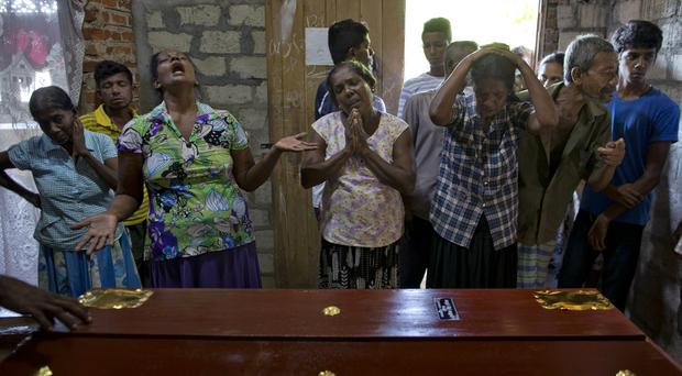 Relatives weep near the coffin of 12-year Sneha Savindi, who was a victim of Easter Sunday bombing at St Sebastian Church (Gemunu Amarasinghe/AP)