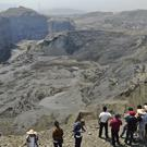 People stand on a ridge overlooking the scene of a mudslide at a jade gemstone mining site (Zaw Moe Htet/AP)