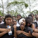 Anusha Kumari, with bandages on her left eye weeps during a mass burial for her husband, two children and three siblings (Gemunu Amarasinghe/AP)