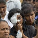 Anusha Kumari, with bandages on her left eye, participates in the burial of relatives (Gemunu Amarasinghe/AP)